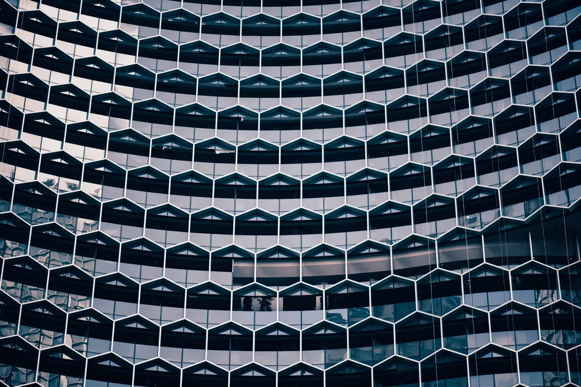 "Selbstorganisation: ""A honeycomb pattern in the facade of a modern office building"" by chuttersnap on Unsplash"